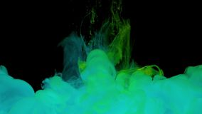 Colorful turquoise and yellow ink drops from above mixing in water. Swirling softly underwater on black background with copy space. Acrylic cloud of paint stock footage