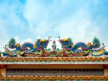 Colorful twin chinese dragon sculpture on the roof in chinese te. Colorful twin chinese dragon statues adorned the rooftops of pavilions in Chinese religious Royalty Free Stock Photography