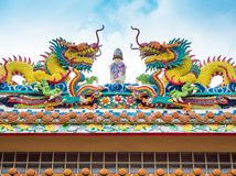 Colorful twin chinese dragon sculpture on the roof in chinese te. Colorful twin chinese dragon statues adorned the rooftops of pavilions in Chinese religious Stock Images