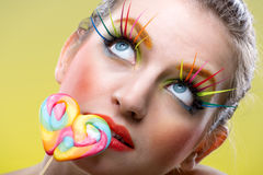Colorful twisted lollipop and colorful extreme fashion makeup Royalty Free Stock Image
