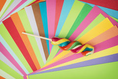 Colorful twisted sweet lollipop and brightly colored papers back Royalty Free Stock Photos