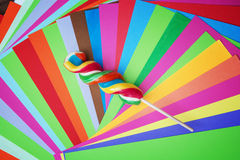 Colorful twisted sweet lollipop with brightly colored papers Stock Images