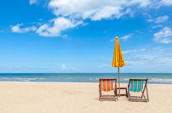 Colorful two beach chairs with sun umbrella on beautiful beach w. Two beach chairs with sun umbrella on beautiful beach with cloudy blue sky. Concept for rest Royalty Free Stock Photography