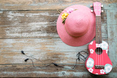 A colorful ukulele and pink hat lay down on the vintage wood background. Royalty Free Stock Images