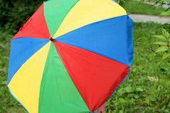Colorful umbrella against green grass. In the summer Stock Image