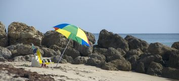 Colorful umbrella on beach. A brightly colored beach umbrella stands solitary on an empty beach stock photo