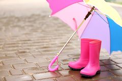 Colorful umbrella and gumboots. On wet pavement Royalty Free Stock Photo