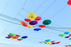 Colorful umbrella hang on electric cable and sky background Royalty Free Stock Photo
