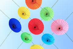 Colorful umbrella hang on electric cable and sky background Royalty Free Stock Photos