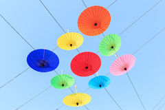 Colorful umbrella hang on electric cable and sky background Stock Images