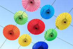Colorful umbrella hang on electric cable and sky background Royalty Free Stock Image
