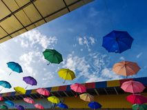 Colorful umbrella Hanging in the sky under the beautiful iron ro stock photos