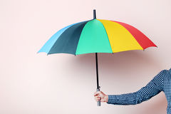 Colorful umbrella. In male hand on beige background Stock Photo