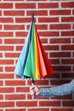 Colorful umbrella. In male hand on brick wall background Stock Photo