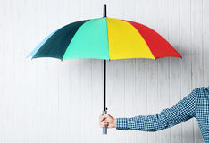 Colorful umbrella. In male hand on wall paneling background Stock Image