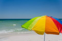 Colorful umbrella at ocean beach shoreline. Scenic tourist travel destination with bright sun protection. Relax and enjoy sun and surf during vacation getaway stock images