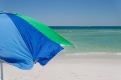 Colorful umbrella at ocean beach shoreline. Scenic tourist travel destination with bright sun protection. Relax and enjoy sun and surf during vacation getaway stock photo