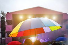 Colorful umbrella in the rain. Outdoor music festival. Rainy weather royalty free stock photo