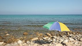 Colorful umbrella on a rocky beach. On the Spanish coast stock video