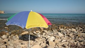 Colorful umbrella on a rocky beach. On the Spanish coast stock footage