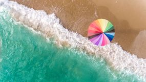 Colorful of umbrella on the seaside beach. Colorful of umbrella on the beach and foam of sea wave from top eye view photo in outdoor sunlight lighting Royalty Free Stock Images