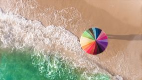 Colorful of umbrella on the seaside beach. Colorful of umbrella on the beach and foam of sea wave from top eye view photo in outdoor sunlight lighting Royalty Free Stock Photos