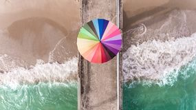 Colorful of umbrella on the seaside beach. Colorful of umbrella on the beach and foam of sea wave from top eye view photo in outdoor sunlight lighting Stock Photos