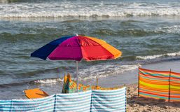 A colorful umbrella spread out on the beach on a beautiful sunny summer day with a rough sea. A colorful umbrella spread out on the beach on a beautiful sunny Royalty Free Stock Image