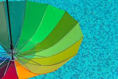 Colorful umbrella on a swimming pool water. Colorful umbrella on a bright blue swimming pool water background Royalty Free Stock Photo
