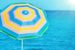 Colorful umbrella on the tropical beach. With blue sea and bright sun as background Royalty Free Stock Photo