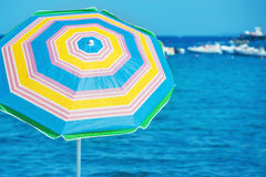 Colorful umbrella on the tropical beach. With blue sea and yachts as background Stock Photography