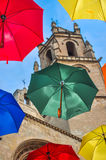 Colorful umbrellas against campanile of gothic basilic. Royalty Free Stock Photo