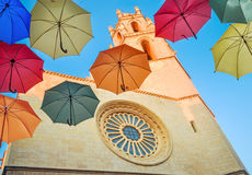 Colorful umbrellas against gothic cathedral and blue sky. Stock Photo