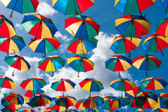 Colorful umbrellas background. Coloruful umbrellas urban street decoration. Hanging Multicoloured umbrellas over blue Royalty Free Stock Photography