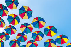 Colorful umbrellas background. Coloruful umbrellas urban street decoration. Hanging Multicoloured umbrellas over blue Royalty Free Stock Photos