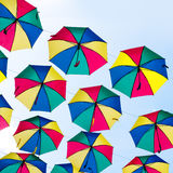 Colorful umbrellas background. Coloruful umbrellas urban street decoration. Hanging Multicoloured umbrellas over blue Stock Image