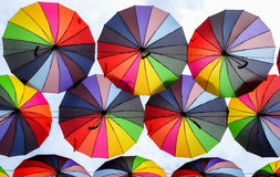 Colorful umbrellas with colors of rainbow in the blue sky Stock Images