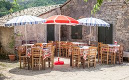 Colorful umbrellas covering the dining tables. Checkered pattern cloth lining the wood. Vacant lot offering food for customers. Co stock photos