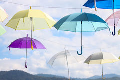 Colorful of umbrellas hang on the sky with blue sky background. Stock Image