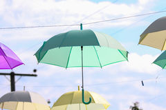 Colorful of umbrellas hang on the sky with blue sky background. Stock Photos