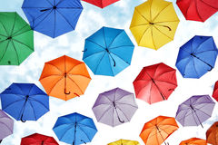 Colorful umbrellas hanging against the sky. Stock Images