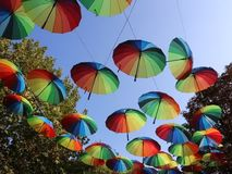 Colorful umbrellas hanging in the breeze. Between trees stock video footage