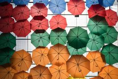 Colorful umbrellas hanging on the ceiling as decoration stock images