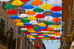 Colorful umbrellas installed on the street in Spanish city. Stock Images