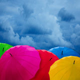 Colorful umbrellas over cloudy sky. Stock Images
