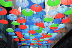 Colorful umbrellas over head Stock Photo