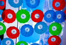 Colorful umbrellas over head Stock Photography