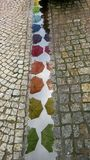 Colorful umbrellas. Reflection of colorful umbrellas in the pudle on the sidewalk after rain Stock Photos