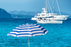 Colorful umbrellas on the tropical beach. With blue sea and yachts as background Stock Image