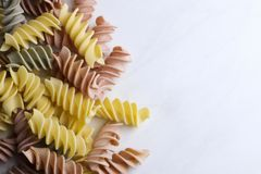 Colorful uncooked pasta on light background royalty free stock photos